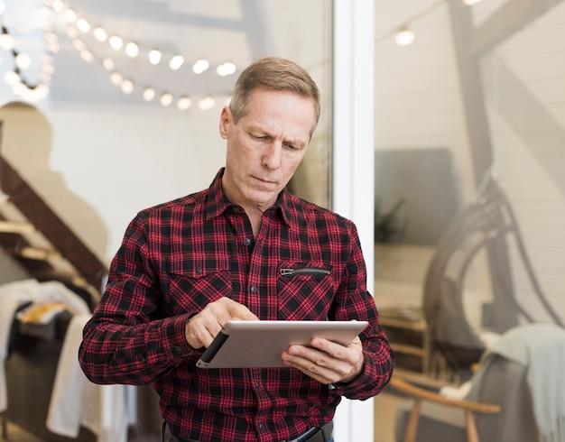 Rijpe mens die op zijn tablet kijkt