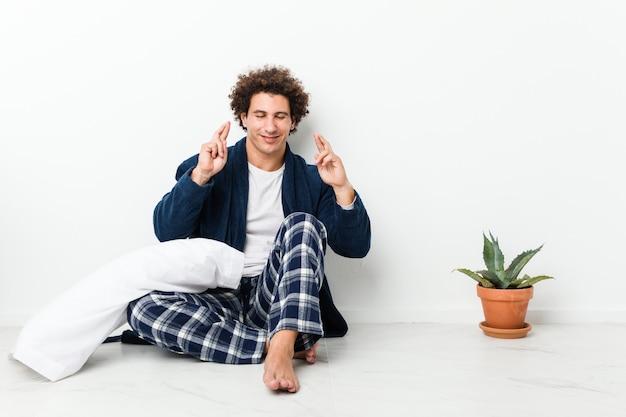 Rijpe mens die pyjamazitting op huisvloer draagt die vingers kruist voor het hebben van geluk