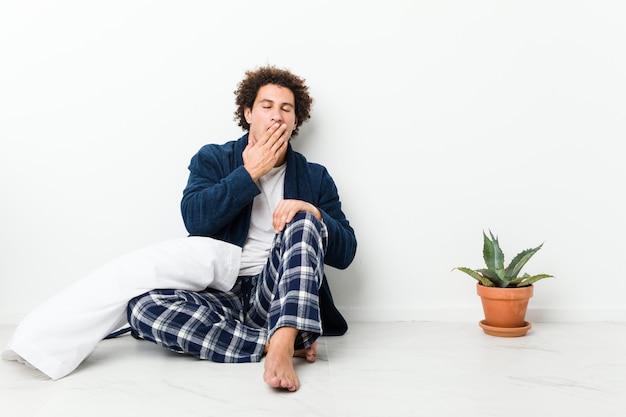 Rijpe mens die pyjamazitting op huisvloer draagt geeuwt tonend een vermoeid gebaar die mond behandelen met hand.