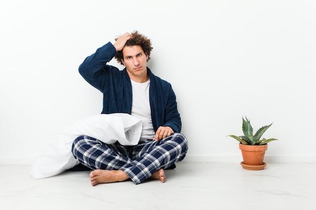 Rijpe mens die pyjamazitting op huisvloer draagt vermoeid en zeer slaperig houdend hand op hoofd.