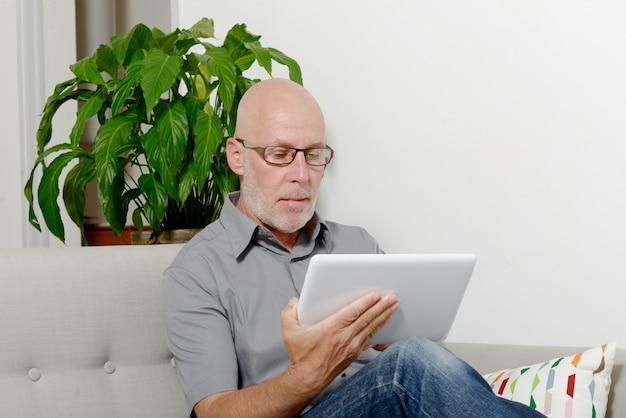 Rijpe mens die thuis op internet websurfing