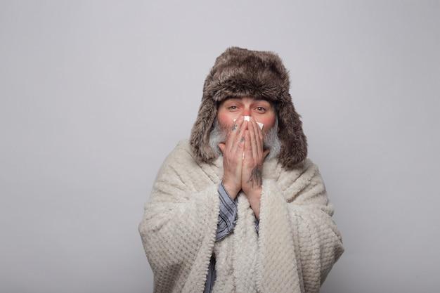 Rijpe mens die zich met een deken en een hoed bedekt die zijn neus met een weefsel blazen
