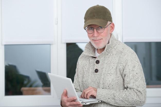 Rijpe mens met honkbal glb die laptop met behulp van