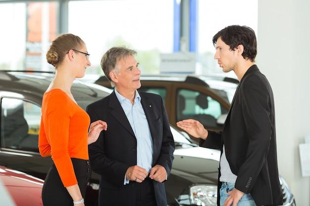 Rijpe mens met jong paar en auto in het autohandel drijven