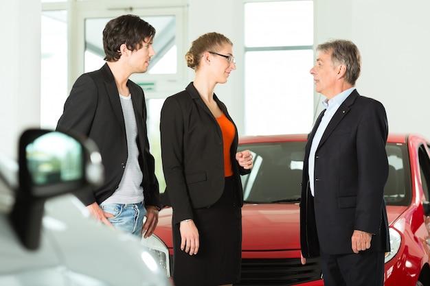 Rijpe mens met jong paar en auto's in het autohandel drijven
