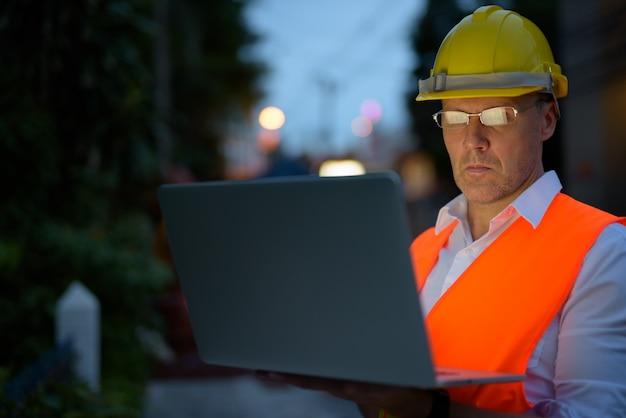Rijpe mensenbouwvakker bij de bouwwerf