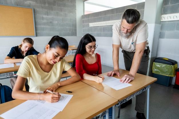 Rijpe middelbare schoolleraar helpt brunette tienermeisje met huiswerk ruimte kopiëren onderwijs