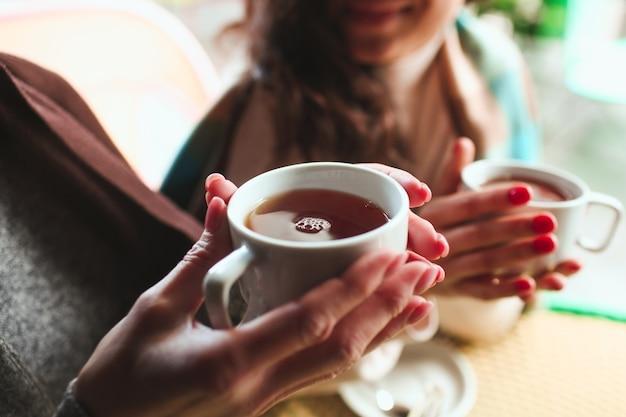 Rijpe moeder en haar jonge dochter zitten samen in café of restaurant. close-up foto van twee paar vrouwelijke handen met kopjes hete thee. zichzelf opwarmen.