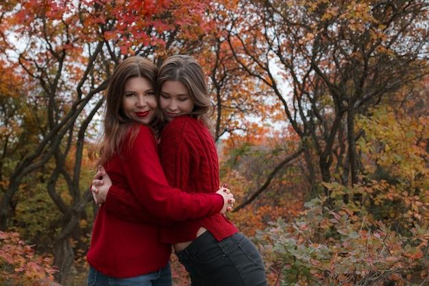 Rijpe moeder knuffelen met haar tienerdochter buiten in de natuur op herfstdag. herfstmode, warme rode truien. wandelen in het herfstbos