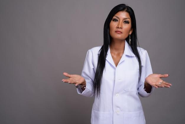 Rijpe mooie aziatische vrouw arts tegen een grijze achtergrond