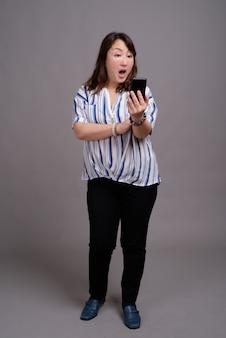 Rijpe mooie aziatische zakenvrouw bedrijf telefoon