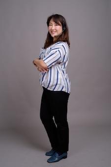 Rijpe mooie aziatische zakenvrouw hoofdtelefoon dragen