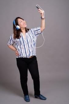 Rijpe mooie aziatische zakenvrouw met koptelefoon en het nemen van selfie
