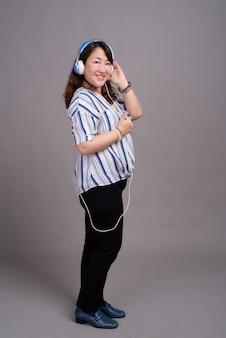 Rijpe mooie aziatische zakenvrouw met koptelefoon