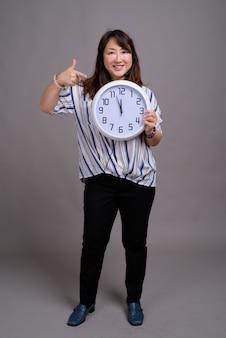 Rijpe mooie aziatische zakenvrouw wijzend op de klok