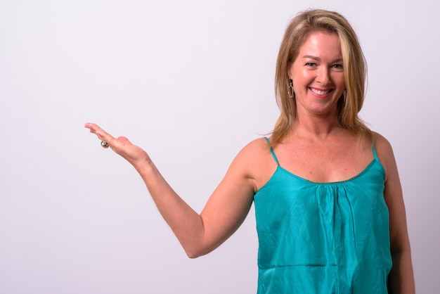 Rijpe mooie blonde zakenvrouw tegen witte ruimte