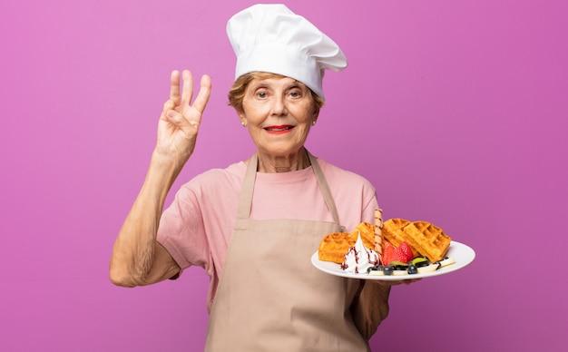 Rijpe mooie oude vrouw die en vriendelijk glimlacht kijkt, nummer drie of derde met vooruit hand toont, aftellend