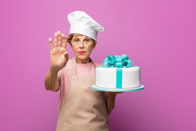 Rijpe mooie oude vrouw die ernstig, streng, ontevreden en boos kijkt die open palm toont die stopgebaar maakt