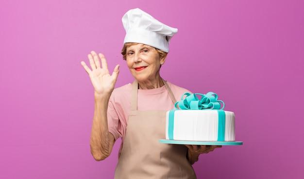 Rijpe mooie oude vrouw die gelukkig en opgewekt glimlacht, hand zwaait, u verwelkomt en begroet, of afscheid neemt
