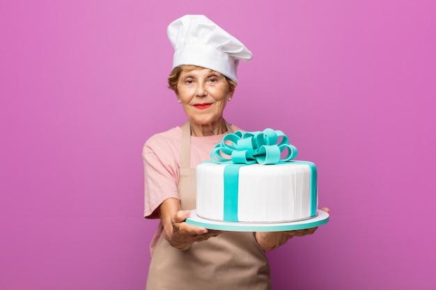 Rijpe mooie oude vrouw die gelukkig glimlacht met vriendelijke, zelfverzekerde, positieve blik, een object of concept aanbiedt en toont