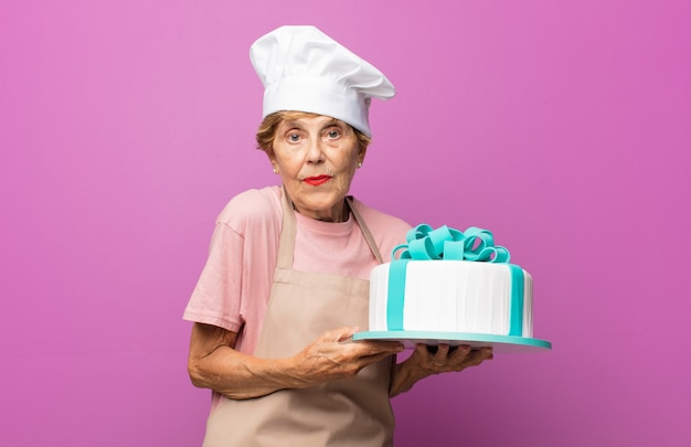 Rijpe mooie oude vrouw die haar schouders ophaalt, zich verward en onzeker voelt, twijfelt met gekruiste armen en verbaasde blik