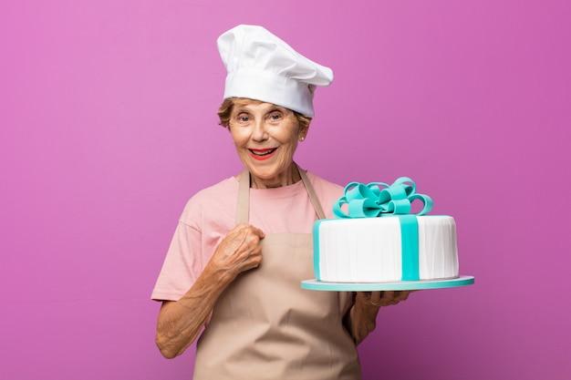 Rijpe mooie oude vrouw die zich blij, verrast en trots voelt en naar zichzelf wijst met een opgewonden, verbaasde blik