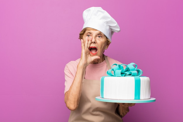 Rijpe mooie oude vrouw die zich gelukkig, opgewonden en positief voelt, een grote schreeuw geeft met handen naast de mond, roept