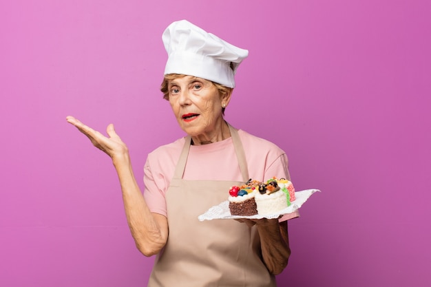 Rijpe mooie oude vrouw die zich verbaasd en verward voelt, twijfelt, weegt of verschillende opties kiest met grappige uitdrukking