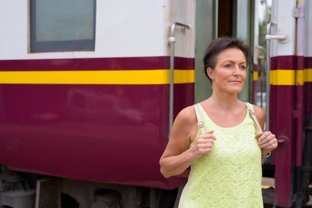 Rijpe mooie scandinavische toeristenvrouw bij station