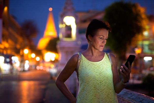 Rijpe mooie scandinavische toeristenvrouw die nakhon pathom onderzoekt