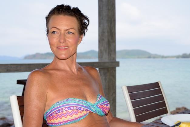 Rijpe mooie toeristenvrouw bij de strandtoevlucht