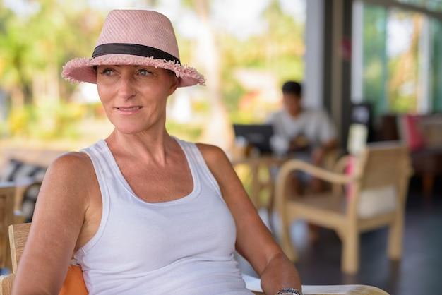 Rijpe mooie toeristische vrouw ontspannen in het resort