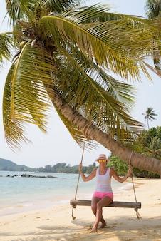 Rijpe mooie toeristische vrouw ontspannen op het strand