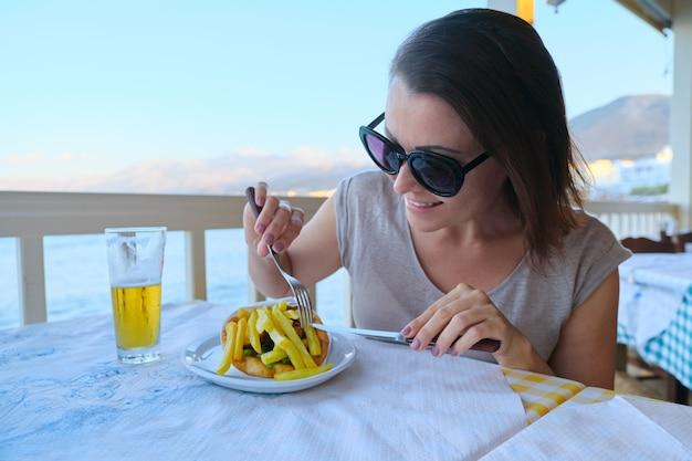 Rijpe mooie vrouw die diner heeft bij badplaatskoffie