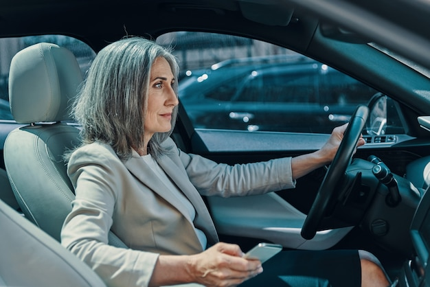 Rijpe mooie vrouw in slimme vrijetijdskleding die lacht en telefoon gebruikt tijdens het autorijden