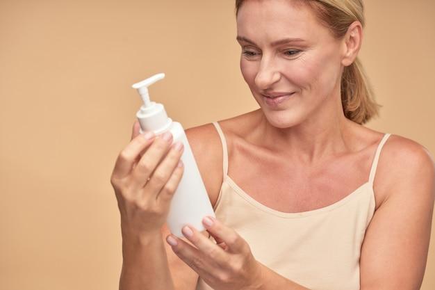 Rijpe mooie vrouw tevreden met cosmetisch product