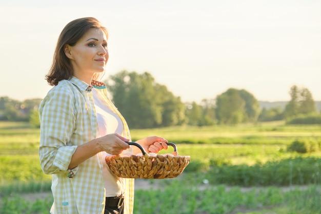 Rijpe mooie vrouwenlandbouwer met mand verse eieren
