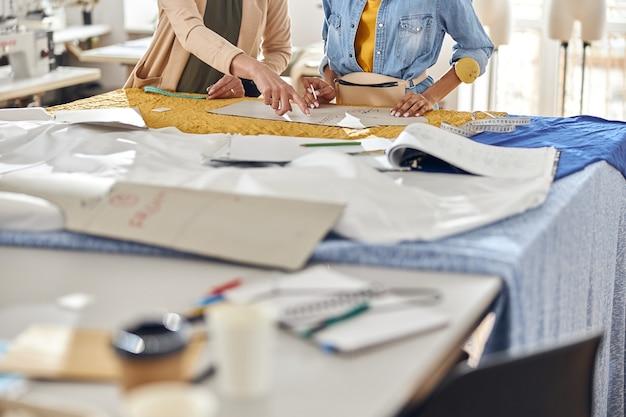 Rijpe naaister leert afro-amerikaanse stagist om patronen op stof te tekenen in werkplaatsclose-up
