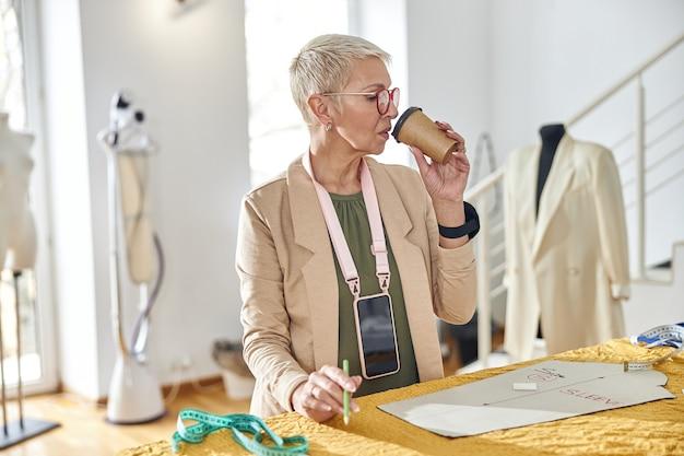 Rijpe naaister met stijlvol kort kapsel drinkt drank aan grote snijtafel in werkplaats