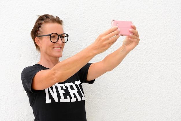 Rijpe nerdvrouw die grote bril draagt en geïsoleerd staat tijdens het nemen van selfie
