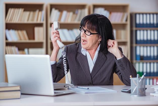 Rijpe onderneemster die in het bureau werkt