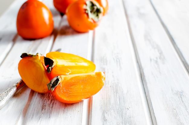 Rijpe oranje dadelpruimen op een oude houten lijst