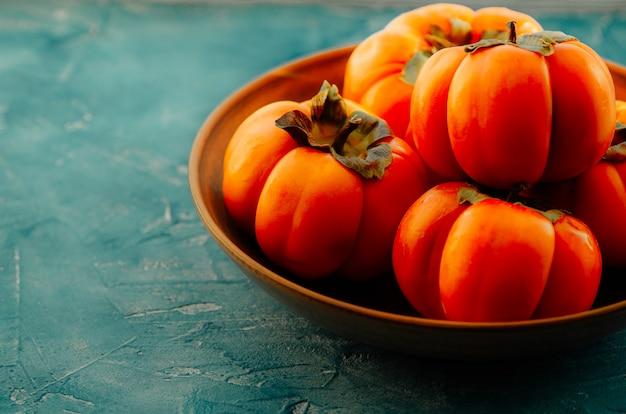 Rijpe oranje persimmon fruit in een keramische plaat. semimon is een bron van calcium