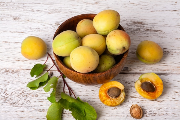 Rijpe organische abrikozenvruchten in asboom houten kom op een witte houten lijst