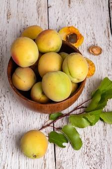 Rijpe organische abrikozenvruchten in asboom houten kom