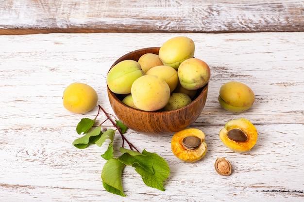 Rijpe organische abrikozenvruchten in de houten kom van de asboom op een witte houten achtergrond