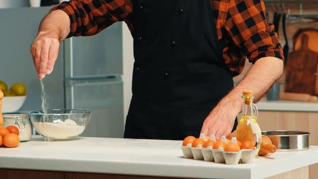Rijpe oude bakker die schort draagt die bloem voor voedselrecept gebruikt. gepensioneerde senior chef-kok met bonete en uniform besprenkelen, zeven zeven rauwe ingrediënten met de hand bakken zelfgemaakte pizza en brood.