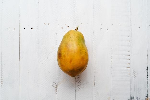 Rijpe papaja op een witte houten tafel, papaja in tweeën gesneden