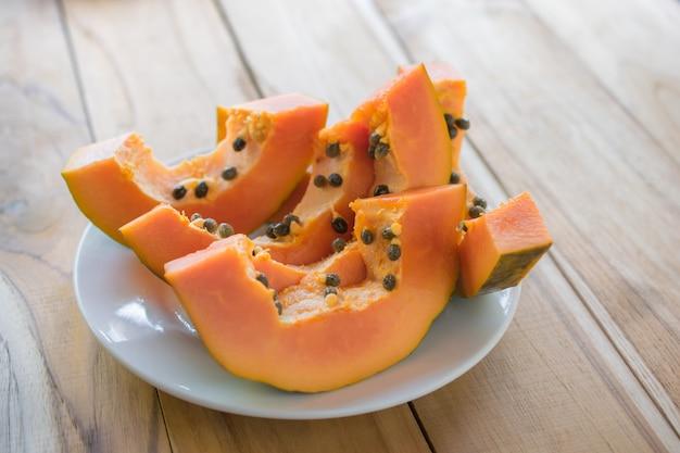 Rijpe papaja op houten tafel, rijpe papaja voordelen voor de gezondheid.