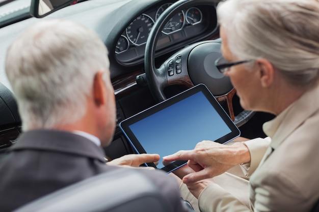 Rijpe partners die aan tablet in elegante convertibel samenwerken
